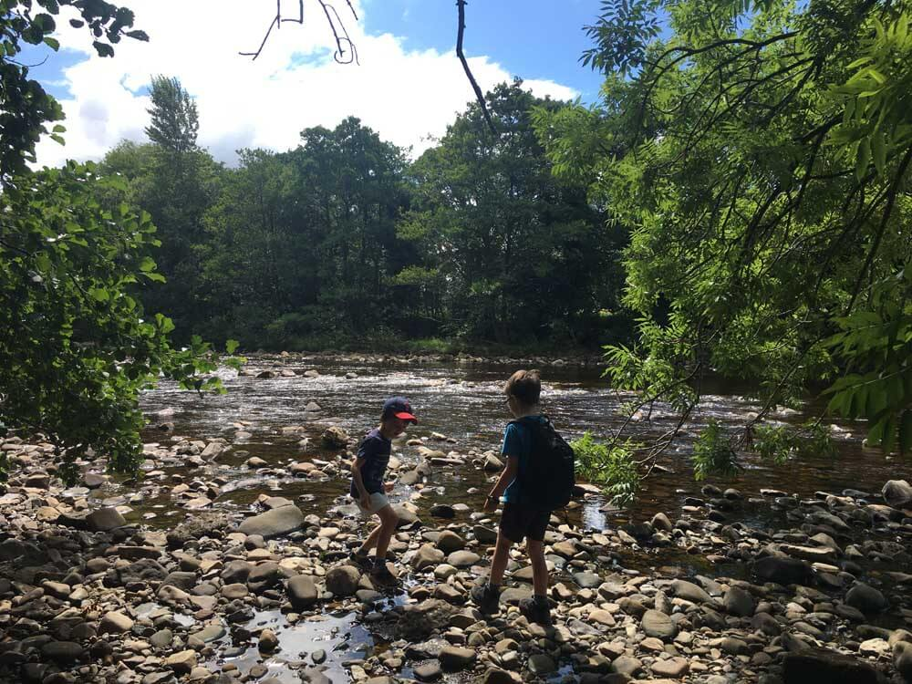Children playing next to the Swale River in North Yorkshire