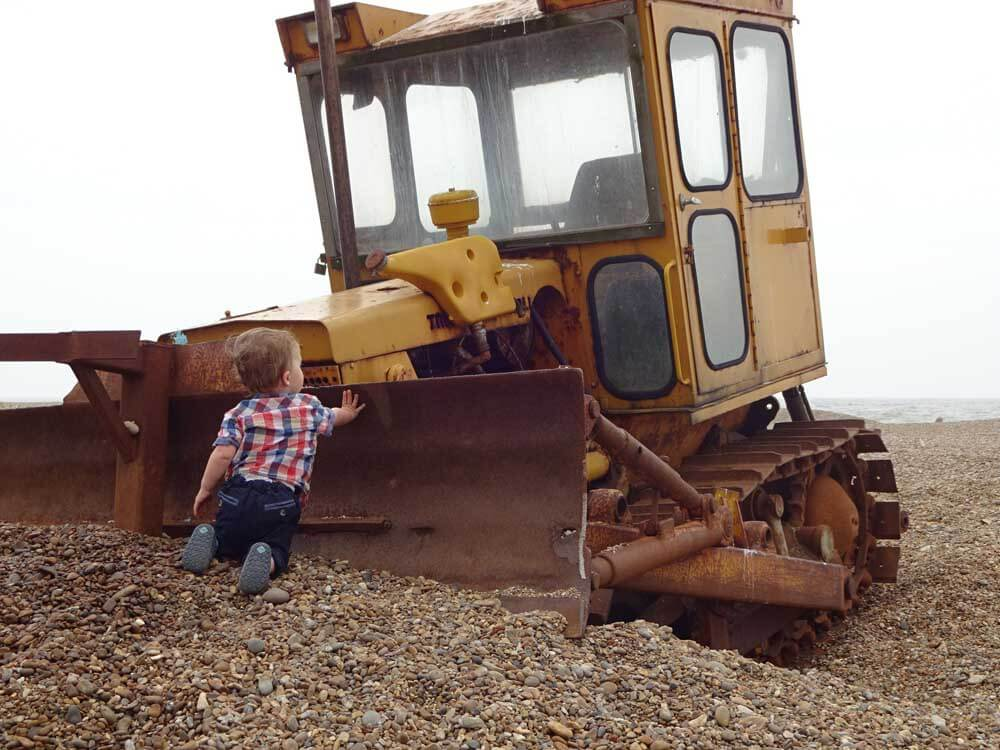 child looking at digger on aldeburgh beach suffolk