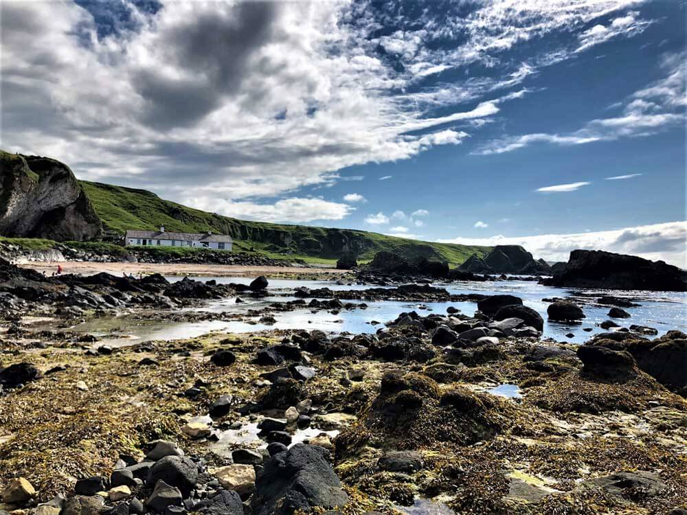 Rocky beach with stone cottages and sea in background