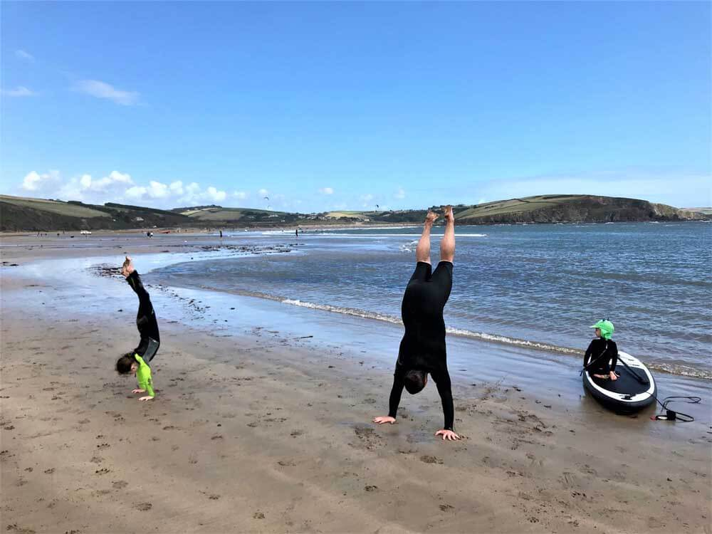 family doing handstands on a beach in Devon