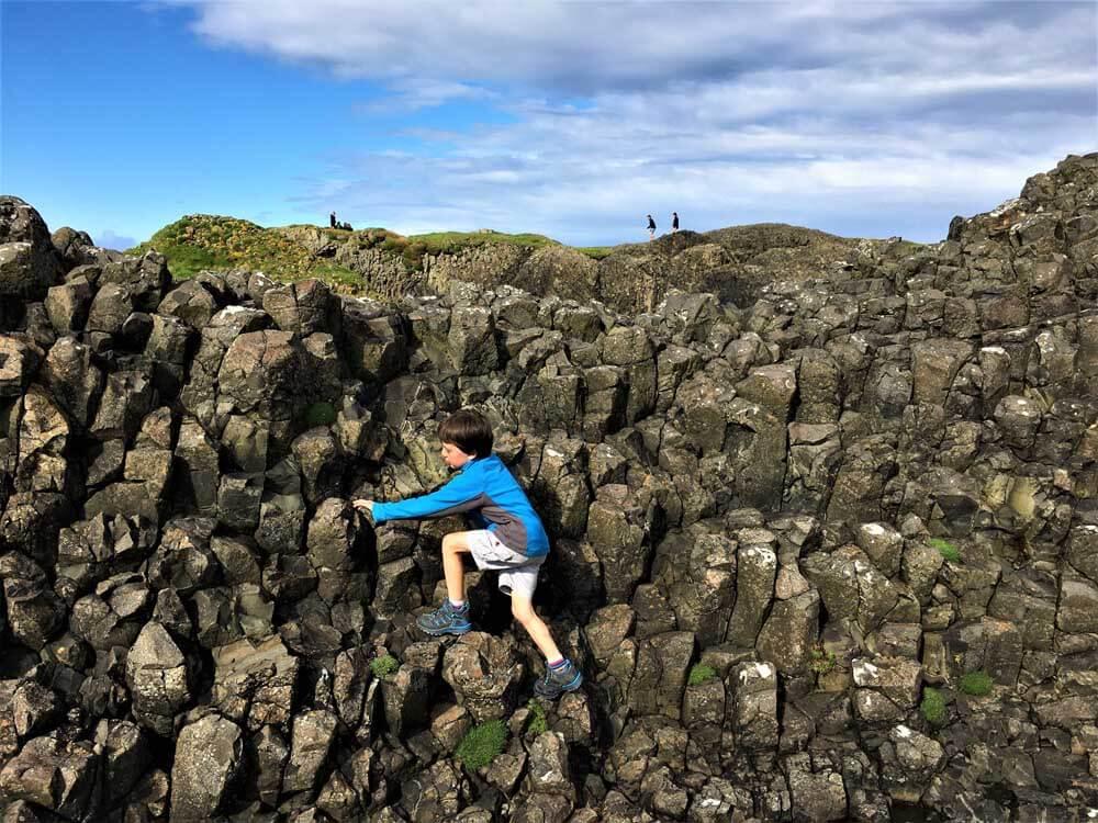 boy climbing on rocks at beach in northern ireland