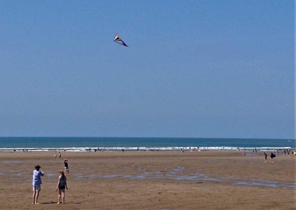 Family flying kite of UK beach break in Croyde