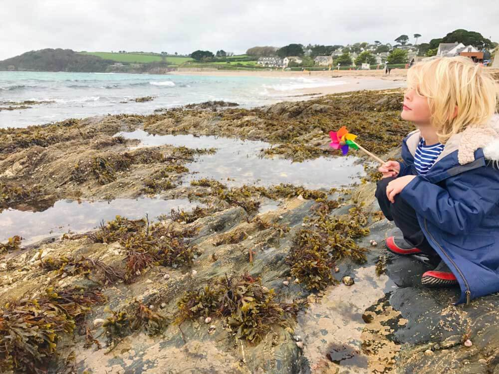 child playing on Gyllyngvase beach in cornwall