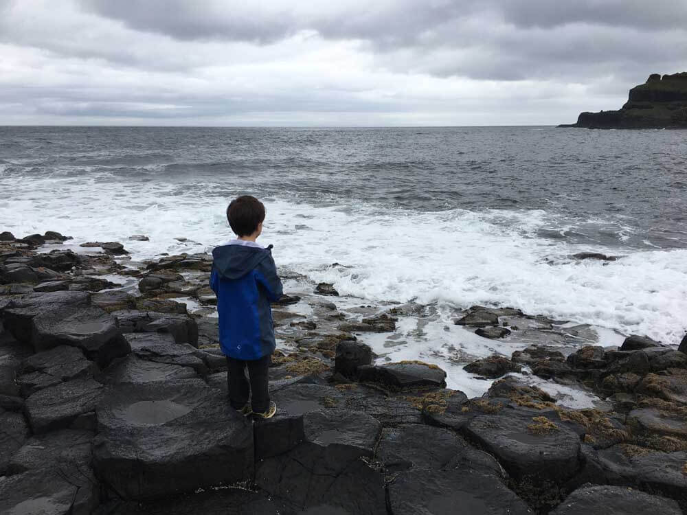 Child looking out to sea from Giants Causeway Northern Ireland