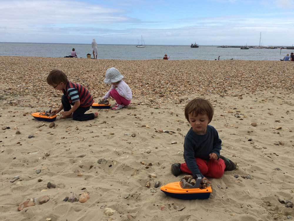 Children playing with toy boats on a UK beach holiday at Lyme Regis in Dorset