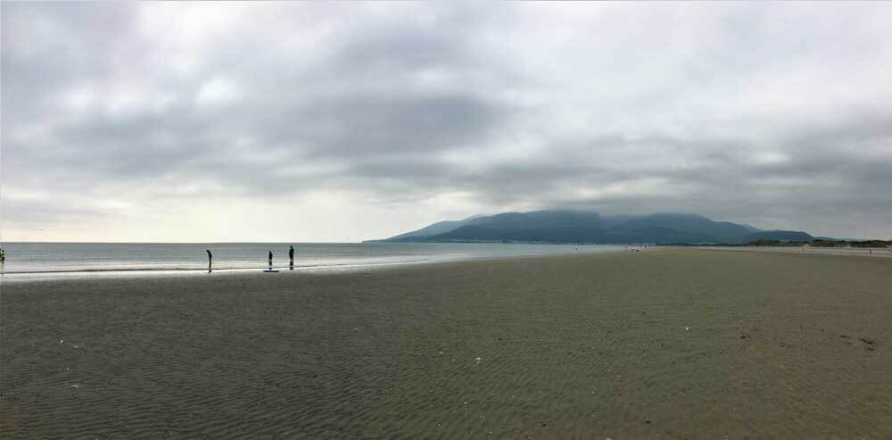 solitary figures on empty beach with mountains in background Northern Ireland