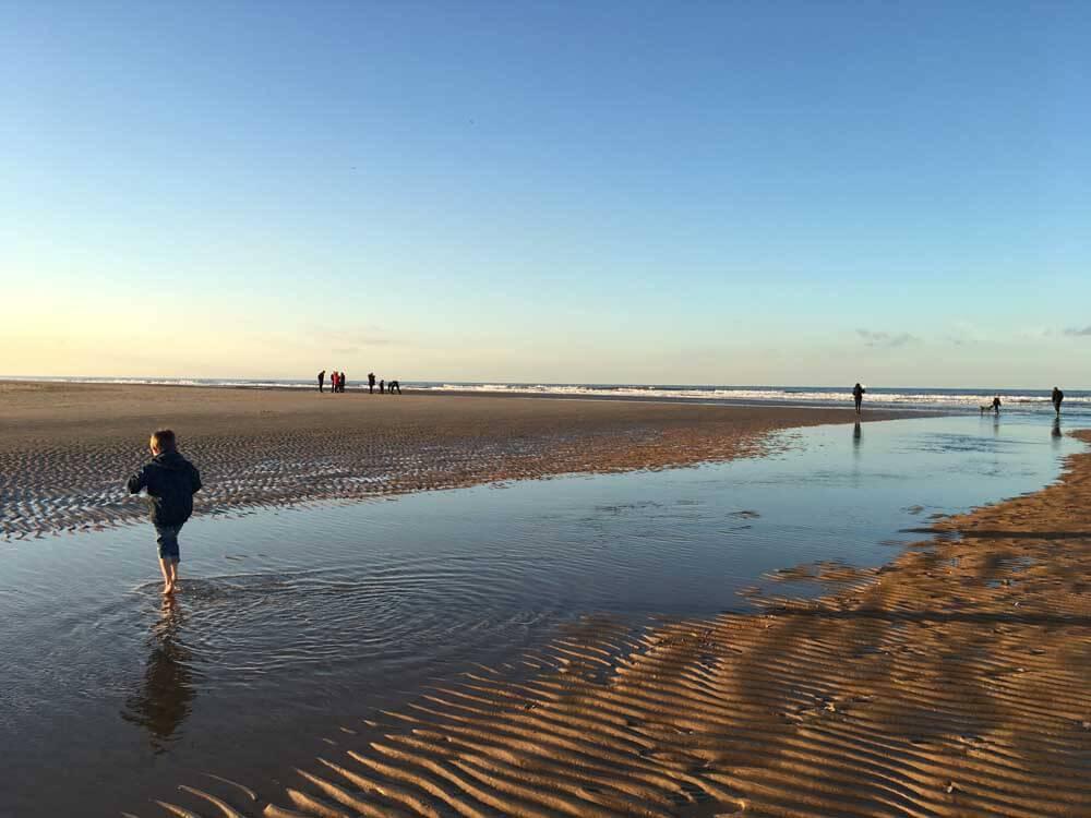 Children paddling at Holkham Nature Reserve in Norfolk