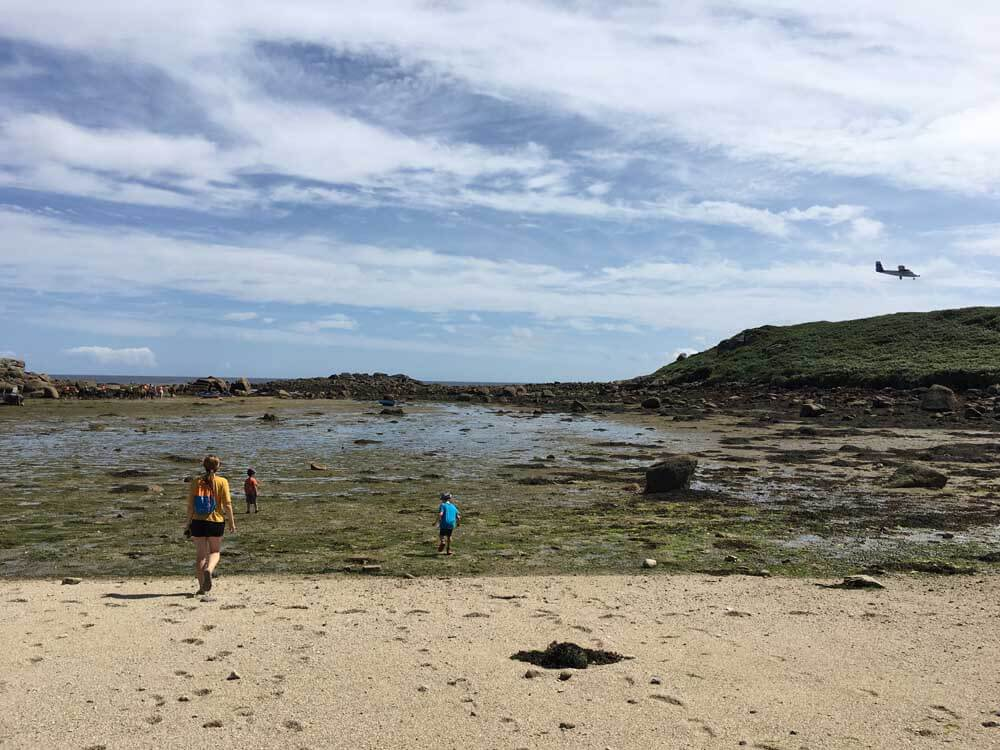 family walking across seaweed on beach in the scilly isles