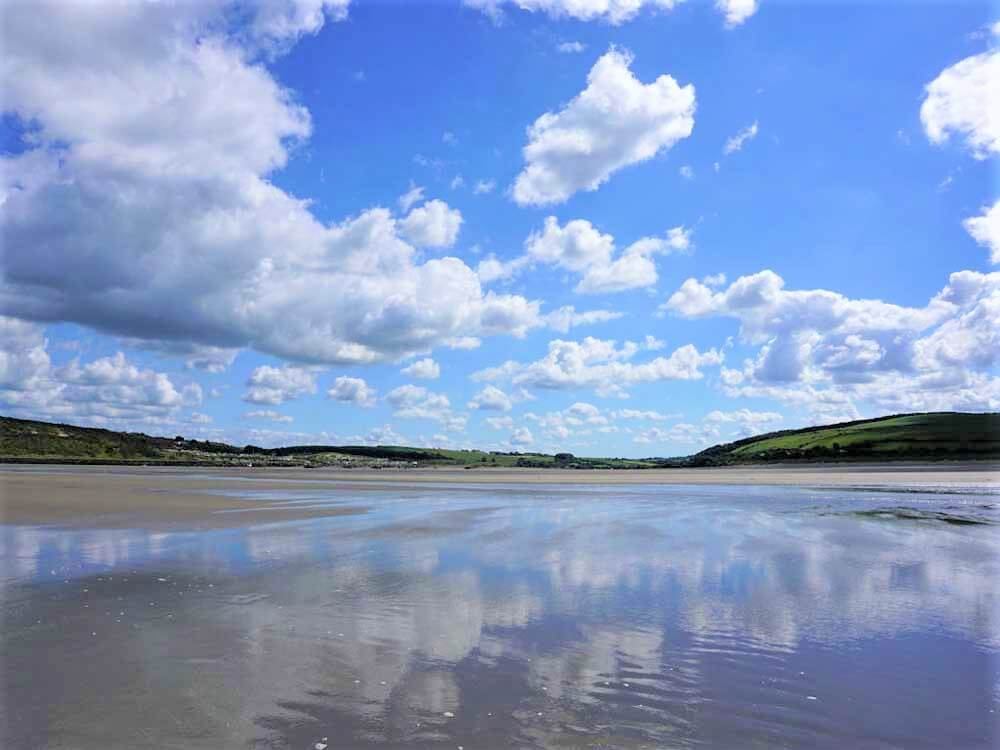 Blue sky reflected in the sea at Poppit Sands in Wales
