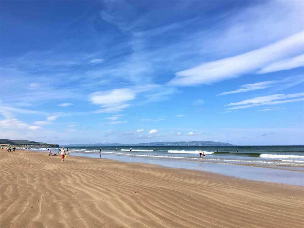 sand beach with breaking waves and blue sky