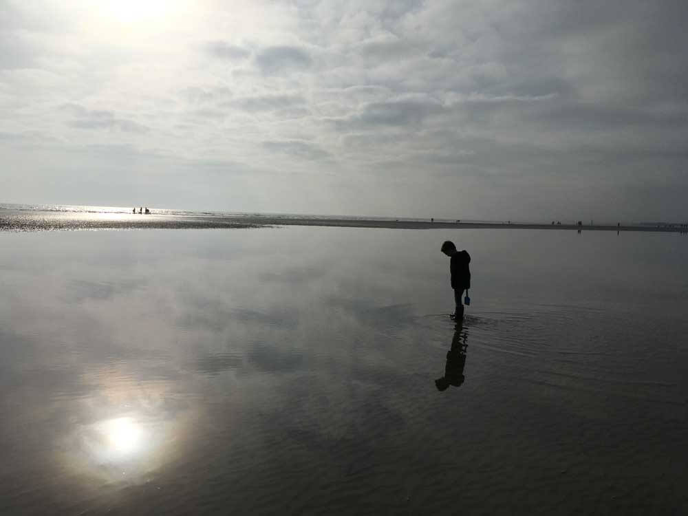 Boy on beach at sunset in East Sussex