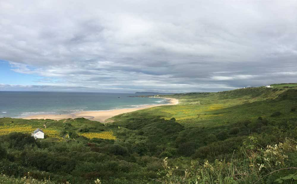 Whitepark Bay with green landscape and sea in background
