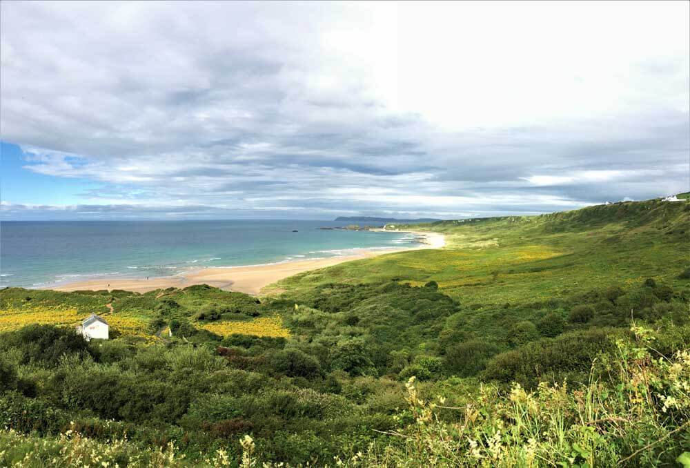Beach backed by green landscape in Northern Ireland