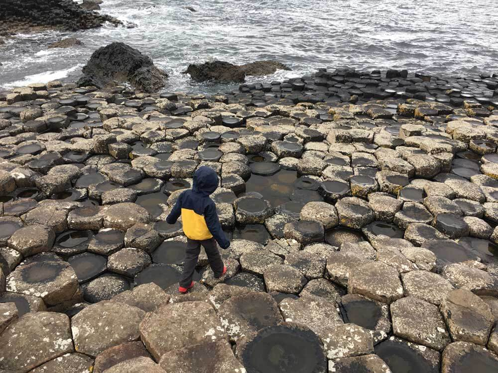 child stepping on Giants Causeway Northern Ireland
