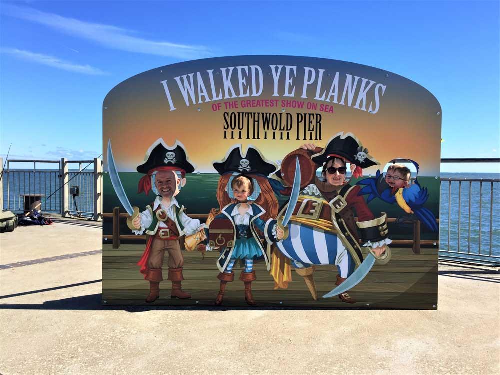 family posing as pirates at Southwold Pier Suffolk UK beach