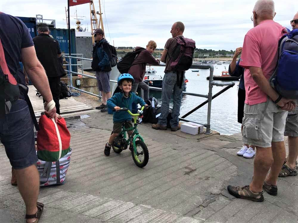 child on bike at St Mary's harbour Scilly Isles