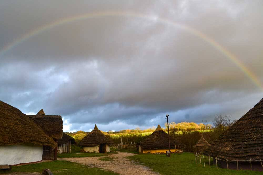 Butser Ancient Farm Open air museum with rainbow in background