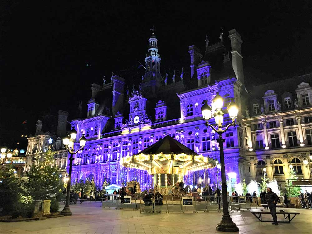 Hotel di Ville in Paris lit up at night Christmas time