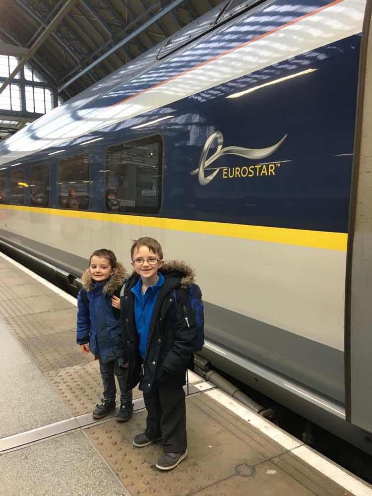 Children standing next to the Eurostar at St Pancras, winter trip to Paris with kids