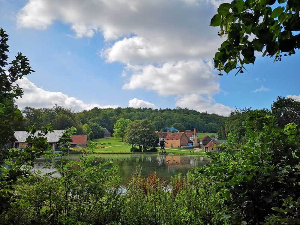 View of millpond with historic buildings in background at Weald and Downland living museum