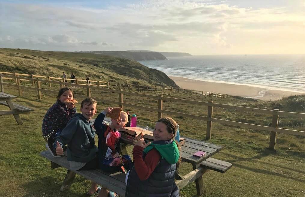 kids eating on bench overlooking sandy beach in cornwall