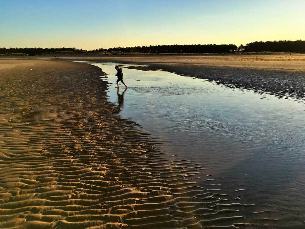 Child paddling at sunset on beach in Norfolk