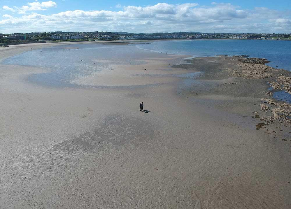aerial shot of people on large sandy beach in Northern Ireland