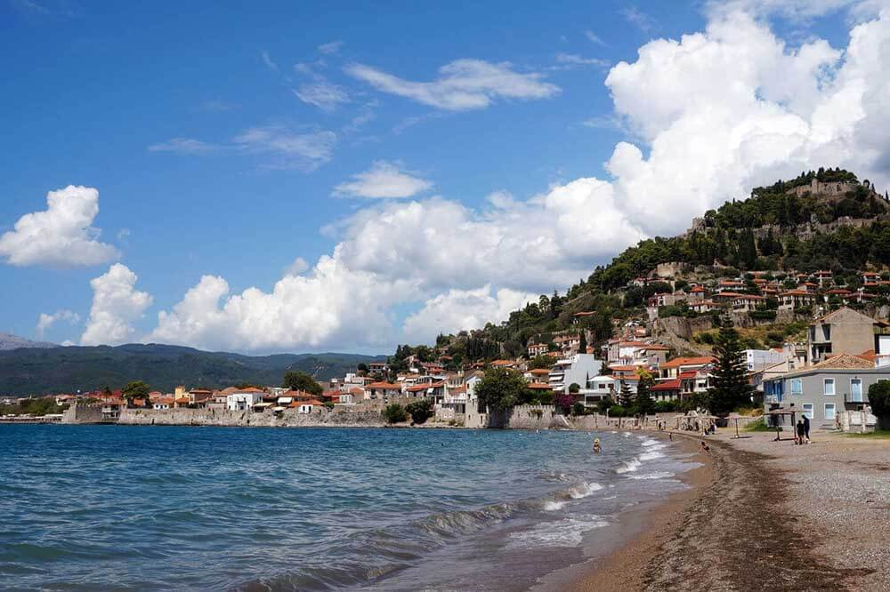 Greek beach with town and hillside in background