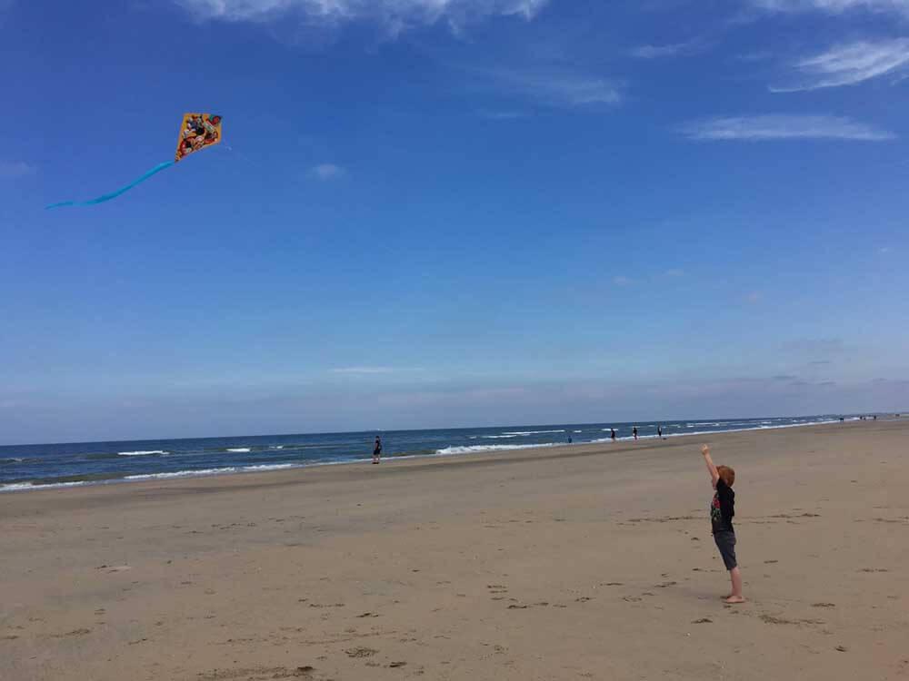 Child flying kite on Zandvoort beach in the Netherlands