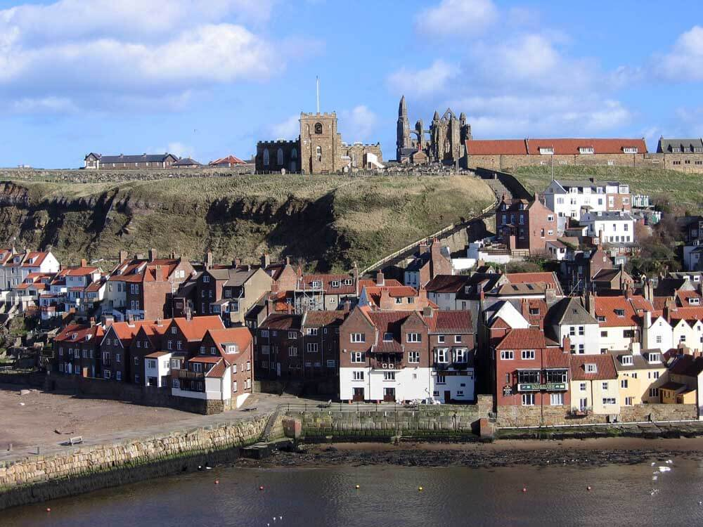 Ruined Whitby Abbey overlooking the harbour, one of the best beach towns in europe