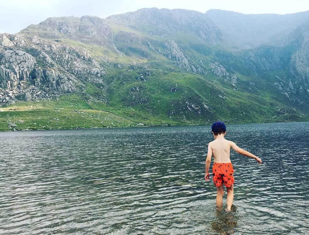 Boy paddling in lake Llyn Idwal in Wales