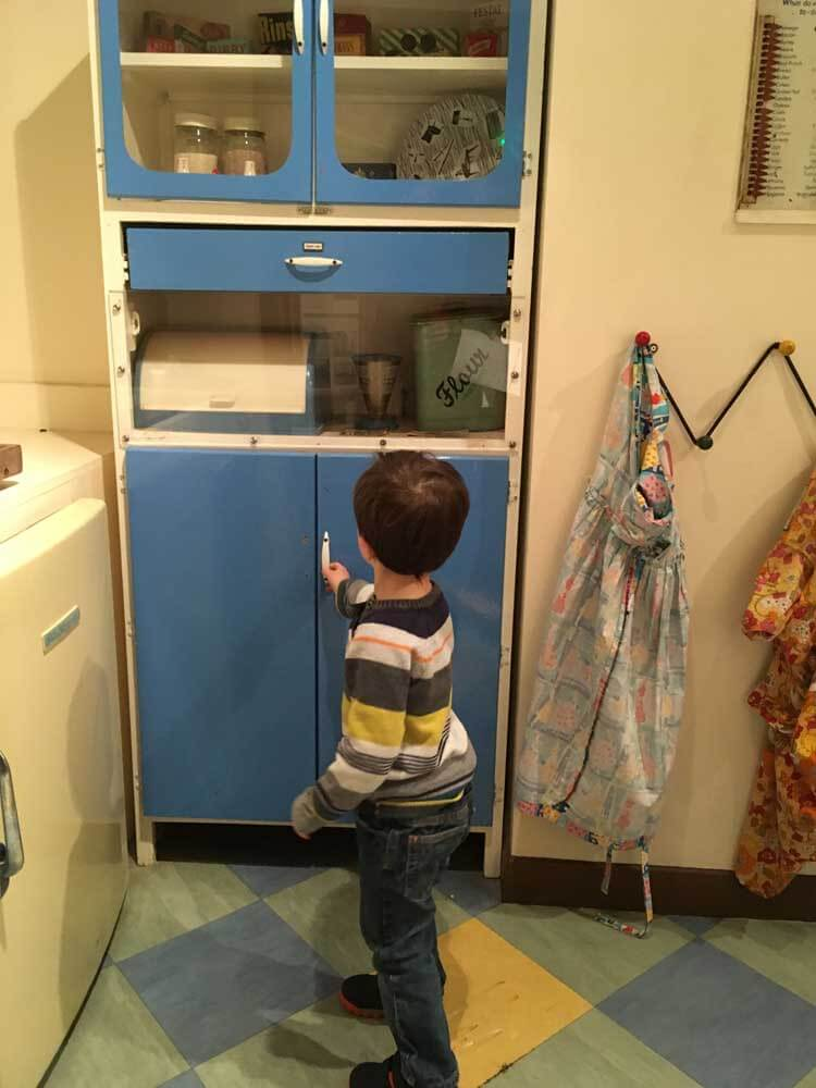 child exploring 1950s kitchen at Stevenage Museum