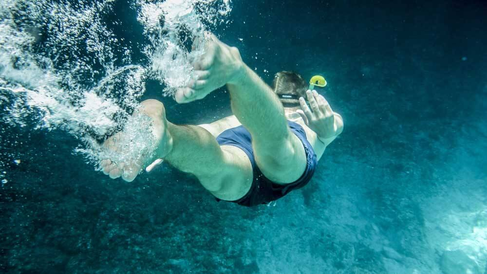 person diving with bubbles