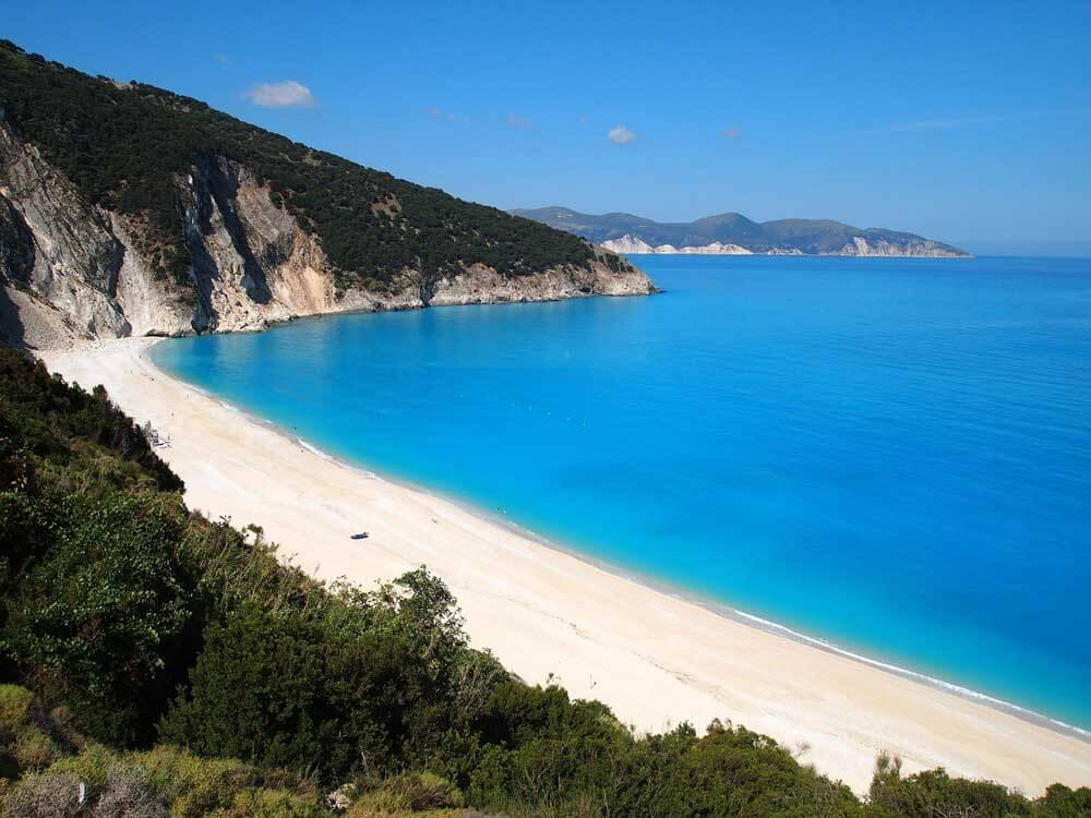 long sandy beach backed by green hills, Myrtos Beach in Kefalonia