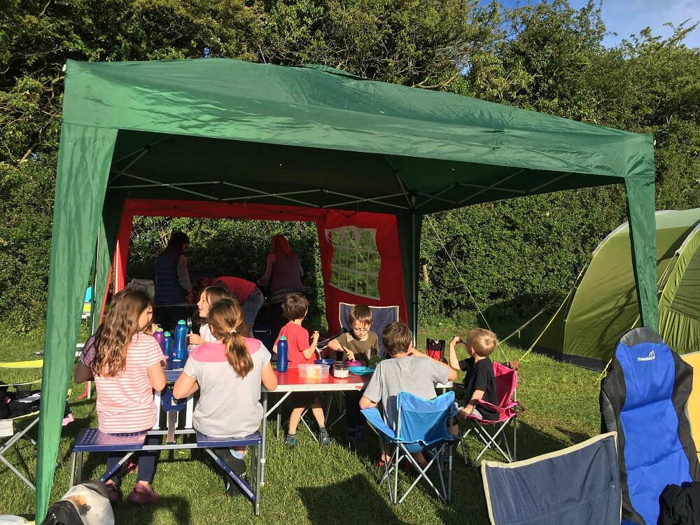 Children eating dinner on campsite under gazebo
