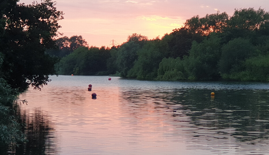pink sunset over open water swimming lake in hertfordshire