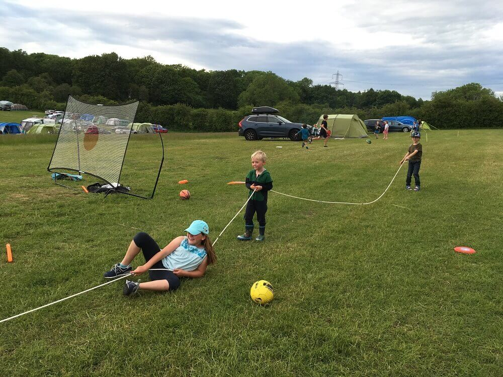 children playing tug of war on campsite