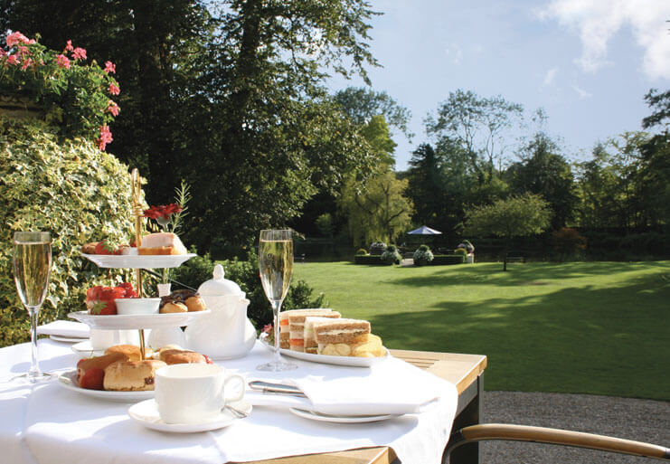 Table laid with traditional afternoon tea outdoors