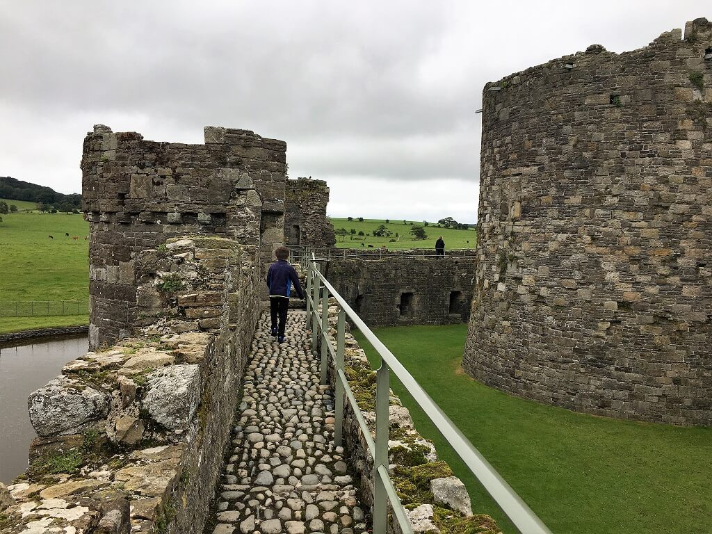 Child walking along parapet at Beaumaris Castle in Wales