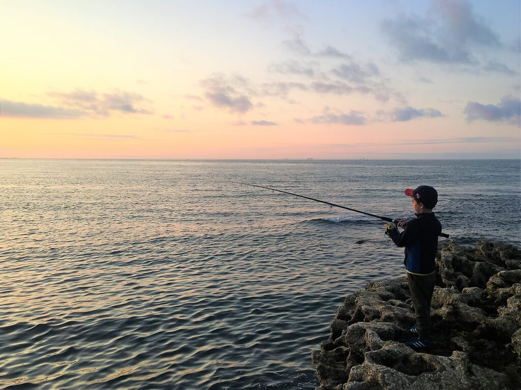 Boy fishing at sunset