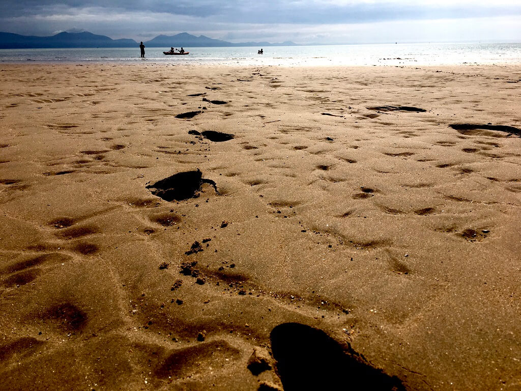 Footprints in sand with sea in distance