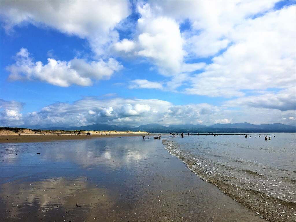 Blue sky reflected onto water on beach in Anglesey Wales