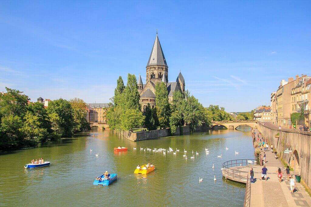 boats on river with church in Metz, France for families