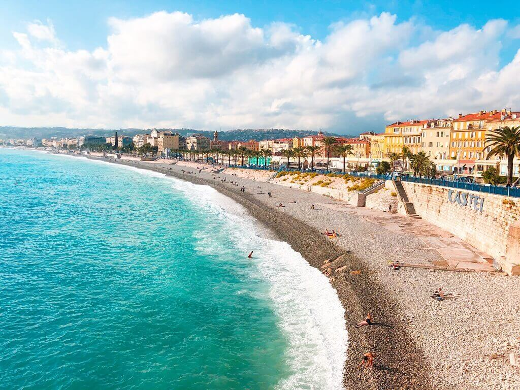 Sea and beach with Nice promenade behind, France family holiday