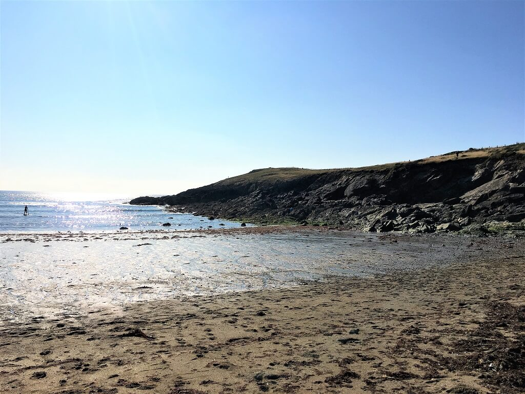 Beach in sunshine with rocky headland in the background