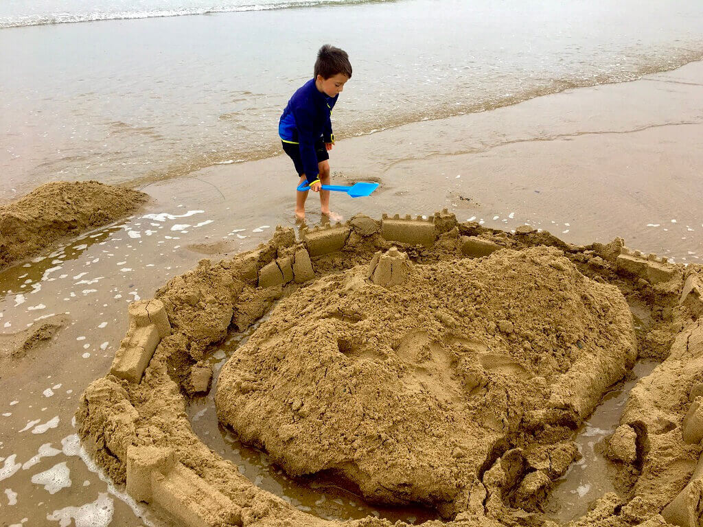 Boy building sandcastle on beach in Anglesey