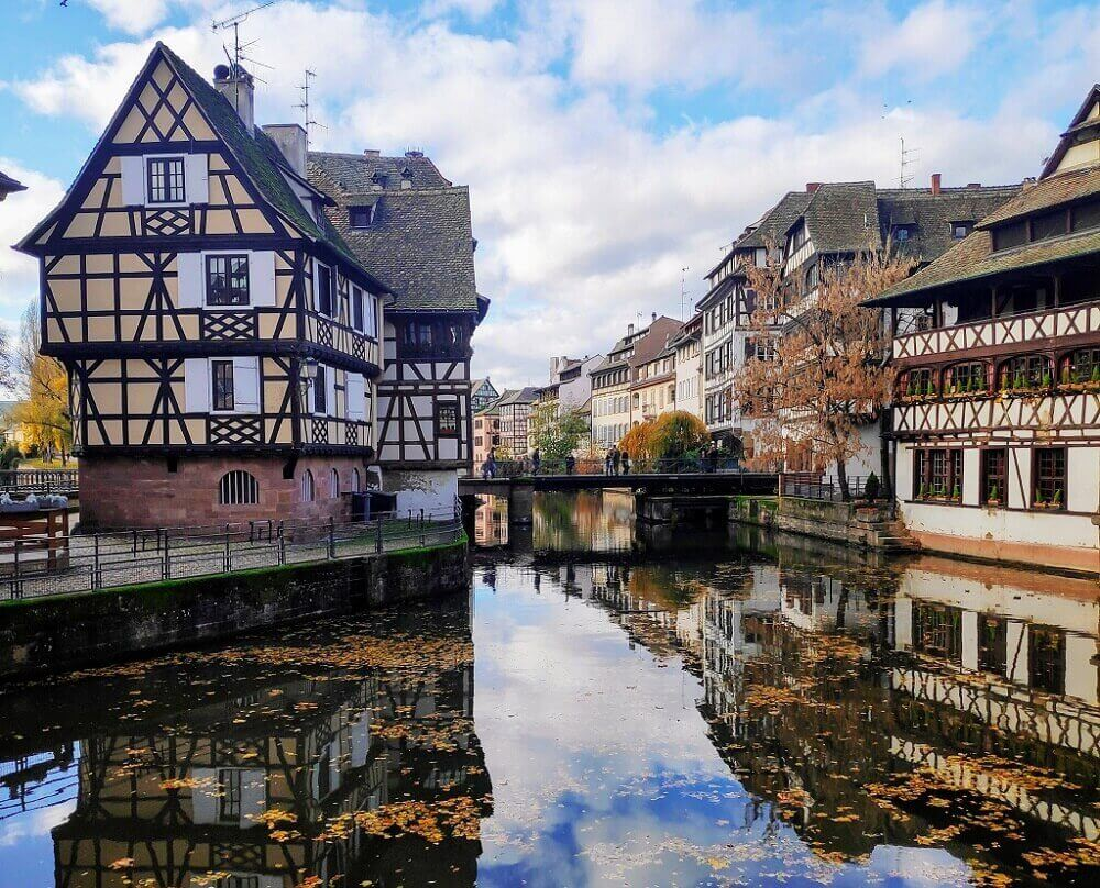 timber framed houses next to river in Alsace region of France for families